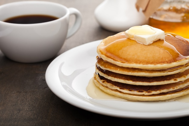 배경에 커피와 버터와 시럽을 넣은 팬케스