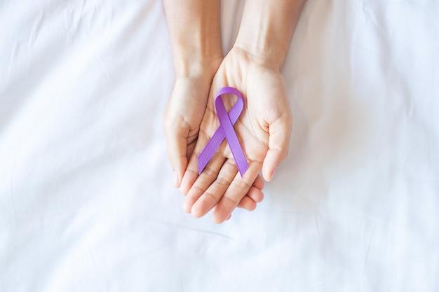 Рак поджелудочной железы, яичко, мир альцгеймера, эпилепсия, волчанка и день насилия месяц осведомленности, женщина, держащая фиолетовую ленту для поддержки людей, живущих. концепция здравоохранения и всемирного дня рака Premium Фотографии