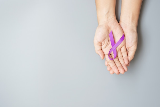 Рак поджелудочной железы, мир альцгеймера, эпилепсия, волчанка и день домашнего насилия месяц осведомленности, женщина, держащая фиолетовую ленту для поддержки людей, живущих. концепция здравоохранения и всемирного дня рака
