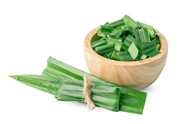 Pandan leaf and slice in wooden bowl isolated on white to taste and aroma in asia food.