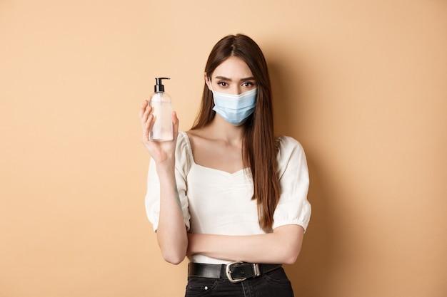 Концепция пандемии и здравоохранения. серьезная женщина, обеспокоенная covid-19, в медицинской маске и демонстрирует бутылку дезинфицирующего средства для рук, стоящую на бежевом фоне.