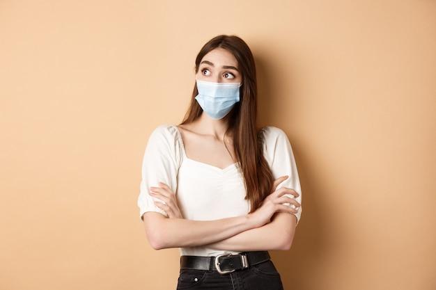 유행성 및 건강 관리 개념. 베이지 색 바탕에 호기심 서 빈 공간 로고를보고 얼굴 마스크에 사려 깊은 소녀.