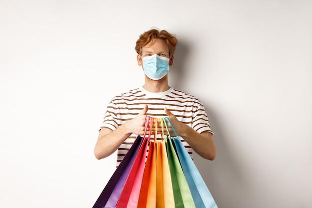 パンデミックとライフスタイルの概念。店で買い物に行く陽気な赤毛の男、医療マスクを着用し、バッグを保持し、白い背景の上に立っています。