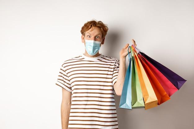 전염병 및 라이프 스타일 개념입니다. 얼굴 마스크를 쓴 잘생긴 청년은 특별 할인에 놀랐고, 쇼핑백을 들고 흥분한 흰색 배경을 응시했습니다.