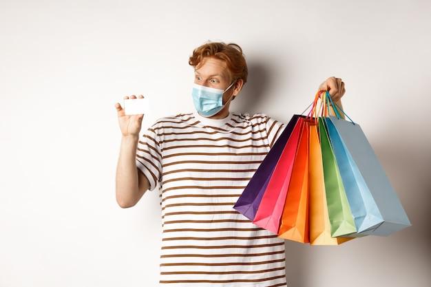 전염병 및 특별 제공 개념. 흰색 배경 위에 서 있는 쇼핑백과 플라스틱 신용 카드를 보여주는 얼굴 마스크를 쓴 행복한 빨간 머리 남자