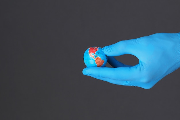 Pandemic concept. hand wears glove holding planet earth. small globe in hand. copy space.