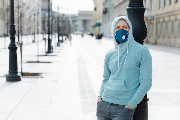 Pandemic coronavirus, covid-19. serious young man dressed in sweatshirt and jeans, wears respiratory mask to protect from virus or infection, walks through empty city streets during quarantine