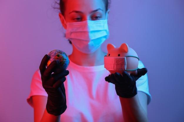 전염병 covid19 테마 장갑을 낀 여성은 의료용 마스크와 글로브 레드블루 네온 그라데이션 라이트가 있는 돼지 저금통을 보유하고 있습니다.