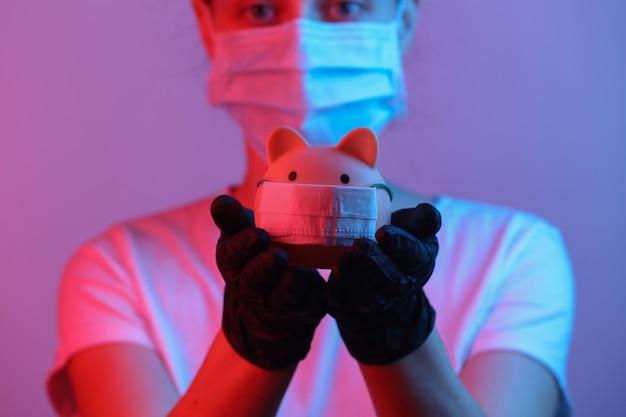 전염병 covid19 테마 장갑을 낀 여성은 의료용 마스크 레드블루 네온 그라데이션 라이트가 있는 돼지 저금통을 보유하고 있습니다.
