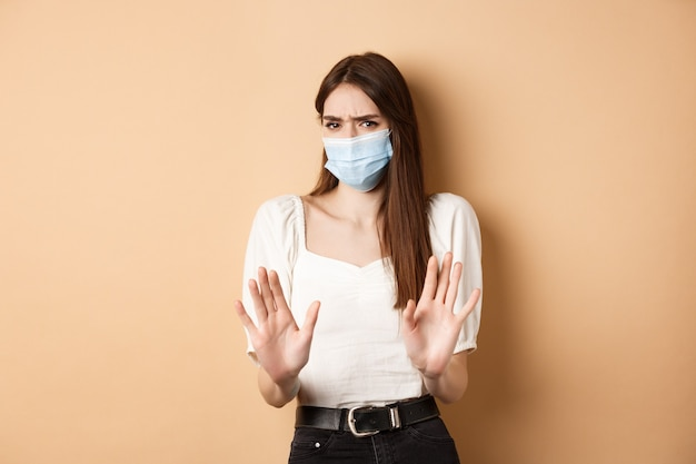 Pandemic and healthcare concept. keep distance. young woman in medical mask stretch out hand in stop sign, telling to stay away and frowning disgusted, beige background.