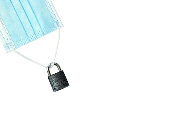 전염병은 흰색 배경 복사 공간에 격리된 닫힌 자물쇠가 있는 의료용 마스크를 쓰고 있습니다.