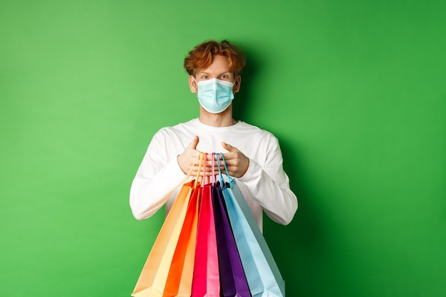 Pandemic and lifestyle concept. cheerful redhead man going shopping in store, wearing medical mask and holding bags, standing over green background.