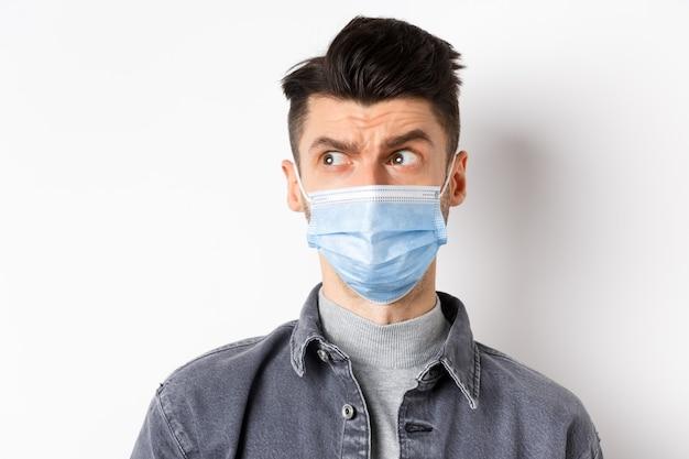 유행성 라이프 스타일, 의료 및 의학 개념. 얼굴 마스크에 혼란 스 러 워 남자는 로고와 흰색 배경에 서 회의적인 인상을 찌 푸 리고 왼쪽 봐.