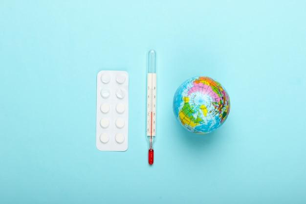 유행성 발발 또는 지구 온난화 개념. 글로브, 온도계 및 파란색 배경에 환 약의 물집. 평면도