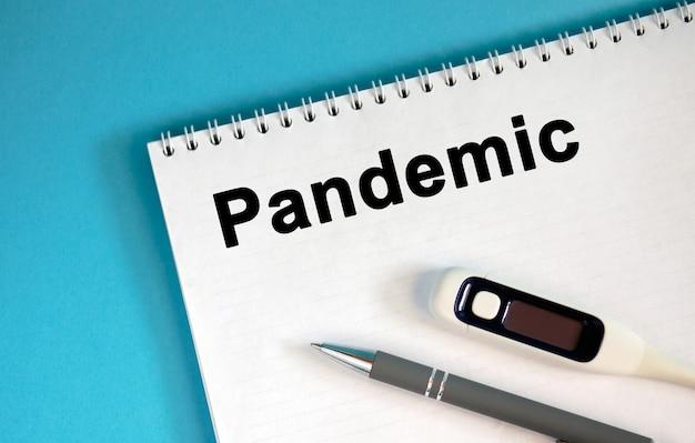 Пандемия - текст в блокноте. положите ручку и медицинский термометр