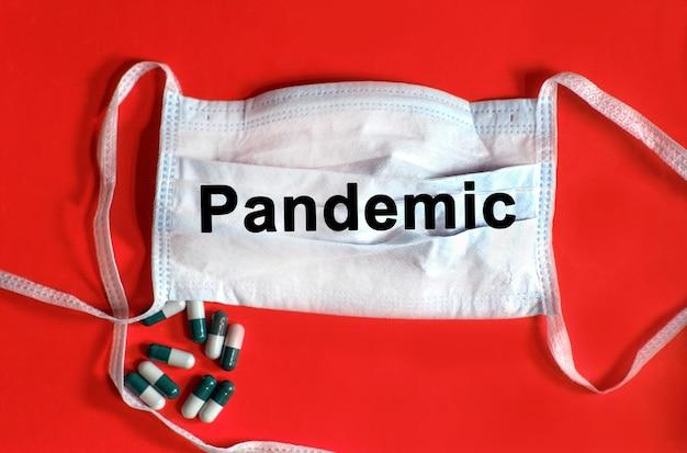 パンデミック-保護フェイスマスクのテキスト、赤い背景のタブレット