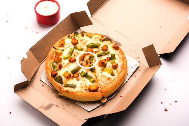 Paneer pizza is an indian version of italian dish topped with cottage cheese, served in a plate with white sauce. selective focus