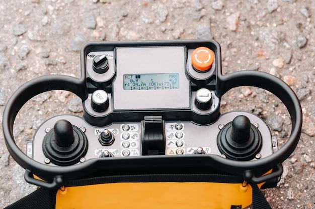 크레인의 텔레스코픽 버킷을 제어하기위한 조이스틱 및 버튼이있는 패널.