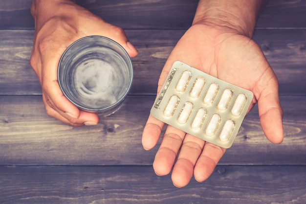 Panels of pills with capsules and glass of water in a male's hand