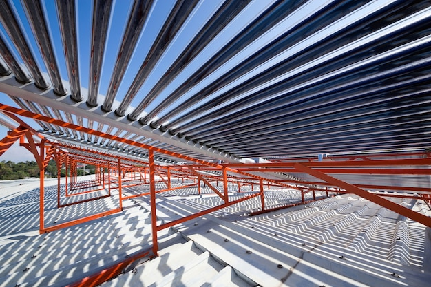 Panels and pipes of the solar water heater on the roof.
