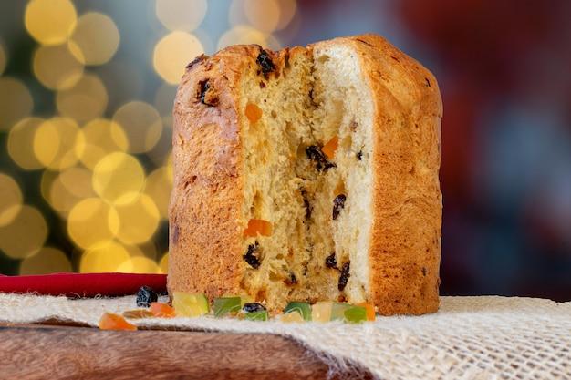 パネトーネ、砂糖漬けの果物とぼやけた背景を持つイタリアのクリスマスケーキ。