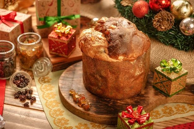 クリスマスの飾りと木製のまな板上のパネトーネ、レーズン、砂糖漬けのフルーツキューブ