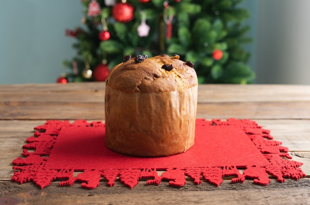 Panettone on red carpet on a wooden table with a christmas tree in the background copy space