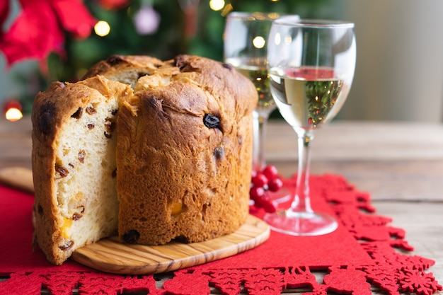 Panettone and white wine glasses on a wooden table with christmas decorations and tree in the backgr...