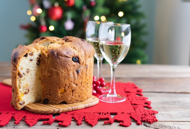 Panettone and white wine glasses on a wooden table with christmas decorations and tree in the background. copy space.