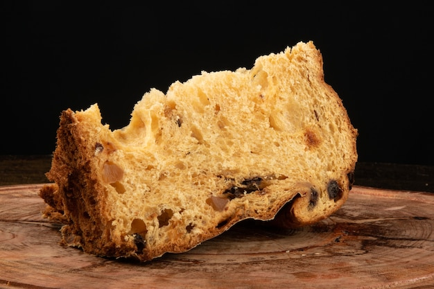 Panettone with sliced traditional christmas food piece with black background.