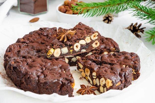 Панфорте. традиционный итальянский рождественский десерт с орехами и сухофруктами на белом фоне. горизонтально, скопируйте пространство.