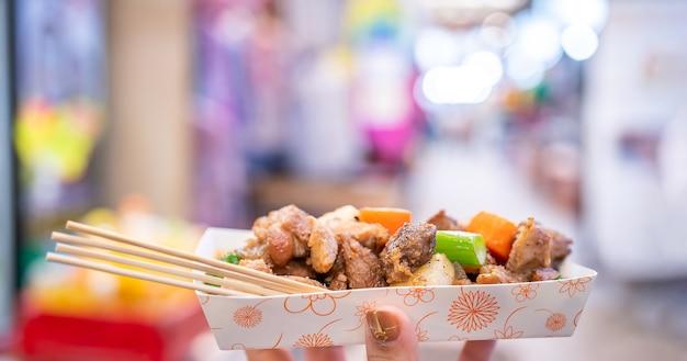 한국 전통 시장에서 panfried 검은 돼지 고기 식사 당근과 샬롯 파와 함께 맛있는 한국 음식 요리 복사 공간을 닫습니다