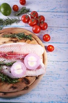 まな板と色の木製テーブルにハーブ、スパイス、野菜とパンガシウスの切り身