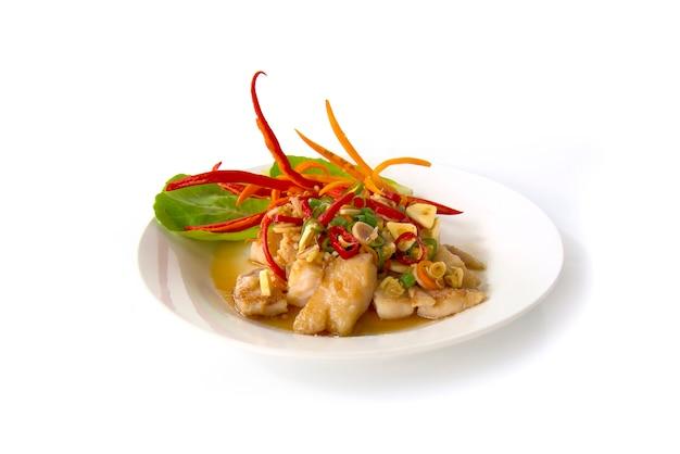 Pangasiusドリーの魚をタマリンドソースで焼き、新鮮なレモングラスをスライスする