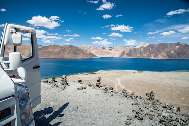 Pangong lake with car and pile of stones