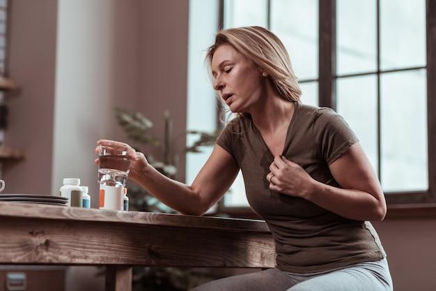 パニック発作。多くのパニック発作に苦しむ金髪の成熟した女性が、薬を飲み、水を飲む Premium写真
