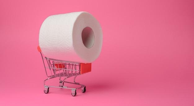 Паническая покупка туалетной бумаги на карантине. рулон туалетной бумаги в игрушечной тележке на розовом фоне. крупный план.