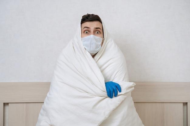保護医療フェイス マスクと毛布で覆う手袋でパニックに陥った若い男 Premium写真