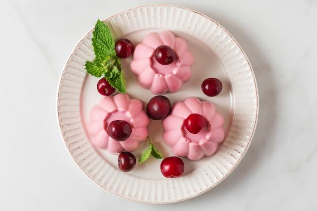 Панна котта десерт с свежей вишни и мяты в тарелку.