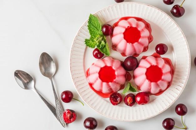 Панна котта десерт со свежей вишней, сиропом и мятой в тарелку с ложками. здоровая итальянская веганская еда. вид сверху