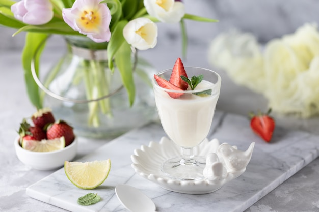 Panna cotta in glass glasses with strawberries on a light background. bouquet of tulips on a white table.