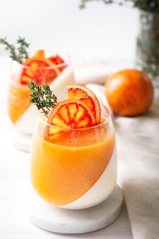 Panna cotta natural desserts decorated with oranges and thyme stand on white