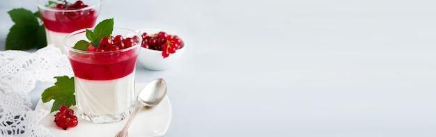 회색 돌이나 콘크리트 배경에 민트와 베리 잎을 넣은 빈티지 유리에 붉은 건포도 젤리를 넣은 판나 코타. 이탈리아 전통 디저트. 선택적 초점입니다.