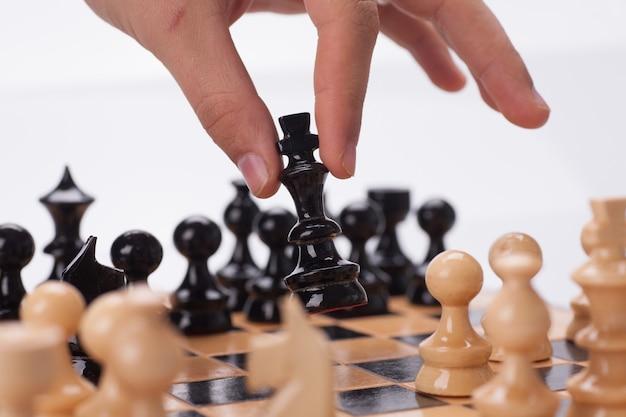 Панорамный снимок шахматной доски с рукой, перемещающей шахматные фигуры.
