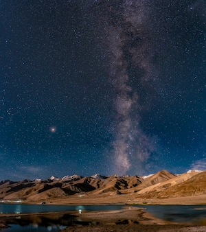 Panorama of arching milky way galactic center over the mountain at pangong lake or pangong tso