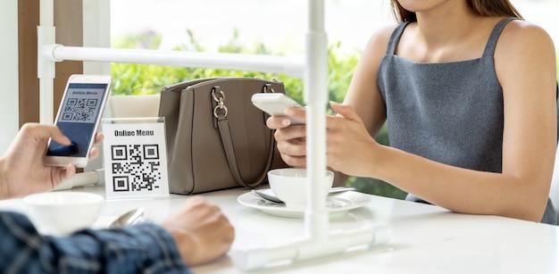 パノラマアジアのお客様はqrコードのオンラインメニューをスキャンします。顧客はレストランの新しい通常のライフスタイルのために社会的距離テーブルに座った