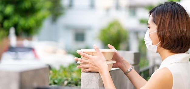 Панорама азиатская женщина с клиентом в маске принимает бесконтактную доставку ящиков с едой