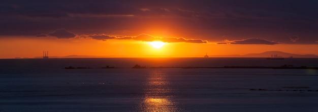 ビーチの夕日、オレンジ色の太陽と青い空のパノラマ。