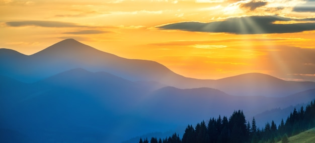 Panorama of beautiful dramatic sunset in the mountains. landscape with sun shining through orange clouds