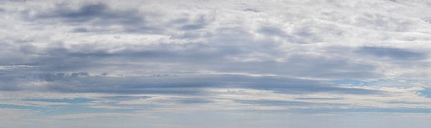 Panorama of blue sky with dense white and gray clouds